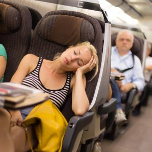 woman sleeping on plane as she travels on vacation